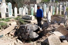 March 27, 2014: A man looks down at an unexploded barrel bomb reportedly dropped by forces loyal to Syria's President Bashar al-Assad at a cemetery in the al-Qatanah neighbourhood of Aleppo. // Mahmoud Hebbo/Reuters