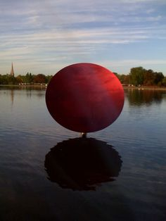 Anish Kapoor's Sky Mirror, Red, 2007, reflects London's sky in from Kensignton Garden's lake