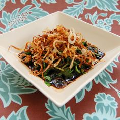A warm salad of sauteed greens with crispy shallots from It's Not Easy Eating Green.