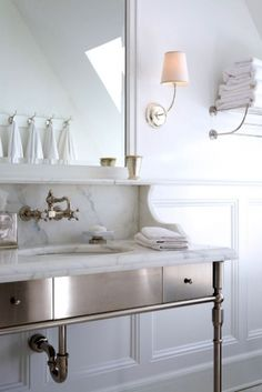 This custom nickel vanity with a marble top gives an updated classic feel to this light and bright bathroom.