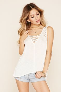 A slub knit top featuring a crisscross V-neckline and back, floral embroidery, sleeveless cut, and a high-low side hem.