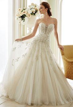 Brides: Sophia Tolli. Strapless tulle A-line wedding dress with deep sweetheart neckline. Illusion panel with rich hand-beading and embroidery and back corset. Dropped waist bodice adorned with matching beading and embroidery that cascades down gathered skirt and chapel train.