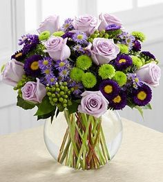 Roses and asters create the perfect bouquet for any of life's special moments. Lavender roses, lavender monte casino asters, purple matsumoto asters, green hypericum berries, green button poms and lush greens create a stunning flower bouquet perfectly arranged in a clear glass bubble bowl vase