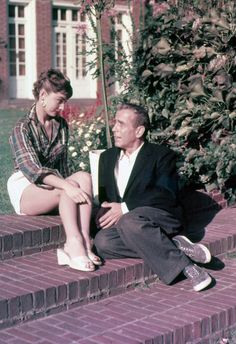 Sneaker Life. Rare color photograph of Audrey Hepburn and Humphrey Bogart during the filming of Sabrina, 1954. Bogart later lends Hepburn his blazer so she can keep warm, as shown in this photograph.
