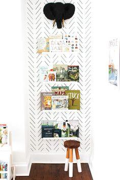 Nursery reading nook with delicate herringbone wallpaper.