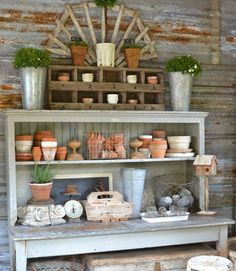 "Inside the garden shed, a potting bench holds dozens of terra-cotta pots and other vintage finds. ""I love how the galvanized wall looks,"" Kathleen writes.   - CountryLiving.com"