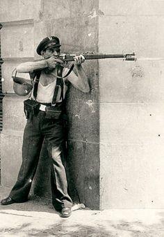 El Guerra Civil estuvo un guerra horrible. Muchos personas combatieron en Barcelona. En esta foto, un soldado republicano apunta un rifle.