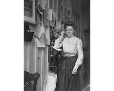 """D.G. Knoop's Tobaksfabrik, værsaagod!"" God gammeldags veggtelefon. Reklame for tobakkfabrikken på veggen, i tillegg til ""Abonnentfortegnelse No. 14"" - den tids telefonkatalog. Foto: Knoop - UBB Billedsamlingen."