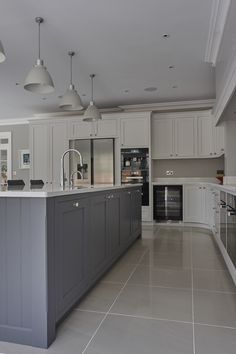 Love the kitchen island in the middle and the color tone - grayish blue with cone shaped ceiling light - lots of storage spaces with shelves