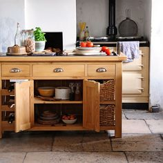 Galway Oak Kitchen Island | The Cotswold Company. Country Style Kitchen with Cream Aga Oven and Oak Kitchen Island with Storage and Wine Rack. Made from hand selected premium oak and oak veneers, it's finished in a light oil to enhance the grain and protect from everyday wear and tear. Storage is not a problem, with the large central cupboard and handcrafted water hyacinth baskets, and there's even space for your favourite vino in the six bottle wine rack.