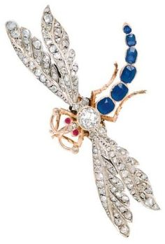 An Antique Sapphire and Diamond Dragonfly Brooch/Pendant , circa 1900.  Designed as a dragonfly centring an old mine-cut diamond weighing approximately 0.85 carat, the body decorated with a row of graduated sapphires, amid rose-cut diamond en tremblant wings and tiny ruby eyes, mounted in silver and 14k rose gold.