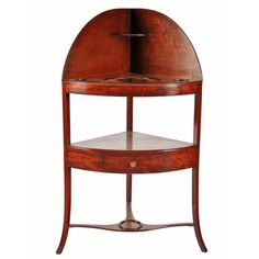 A George III mahogany corner washstand with ebony stringing decoration. The top shelf has three circular cut outs to take a washbowl and two side dishes while the middle shelf is fitted with a bow-fronted drawer. The lower cross stretcher has a circular dish stand. The washstand is in good condition. (Circa 1800) Height 117cm (46.1 inches)Width 65cm (25.6 inches)Depth 45cm (17.7 inches)
