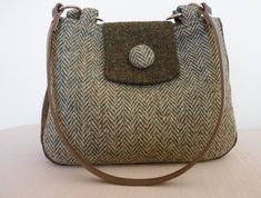 """Harris Tweed Bag/£44 by ladjatweedcraft. Small rounded handmade Harris Tweed handbag in lovett herringbone with a green mix contrast tab and gusset band, brown poly cotton lining with small inner pocket and 1/2"""" brown leather handles which are long enough to go over one shoulder and short enough to be carried as a handbag. Measurements – 9 ½"""" wide x 7 ¼"""" deep with all round gusset. Handle length approx 24"""" including loops & rings."""