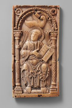 """Plaque with Saint John the Evangelist [Carolingian; Made in Aachen] Early 9th Century during the time of Charlemagne.  An ivory plaque of St John the Evangelist.  The book is inscribed """"In the beginning was the Word.""""  Heilbrunn Timeline of Art History 