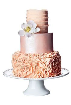 Blush colored wedding cake with ruffles and magnolia topper by Sweet Grace Cake Designs