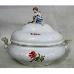 Belíssima sopeira em porcelana alemã, marca da manufatura de Meissen, com trabalhos em relevo e pintura floral em policromia. Pegador da tampa na forma de Puttino. (pescoço do Puttino colado). Med. 30,5x38x24cm.