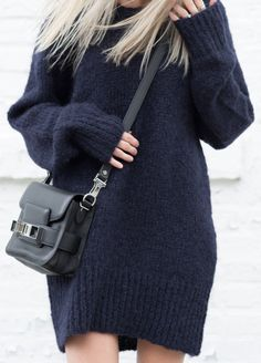 Figtny is wearing an oversized knit blue sweater from Aritzia and a bag from Proenza Schouler