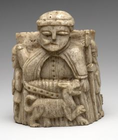 Chess-piece; ivory; king seated on throne; wears mantle fastened at neck, originally held horn to lips with right hand, broken off; man-at-arms to each side; dog before king. Museum number 1856,0612.2 14thC-15thC  Made in: Scandinavia (?), carved ivory Height: 72mm Width: 65mm
