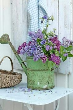 Beautiful cottage display. Love the shabby green painted watering can filled with lilacs.