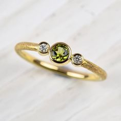 A beautifully elegant, hand made 18ct yellow gold ring set with a green tourmaline and diamonds.
