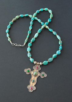 A long cross necklace featuring turquoise gemstone beads with a gold-washed vintage sterling silver Turkoman cross pendant that is both classic and bohemian chic. $375.00  Modern ethnic jewelry by Angela Lovett Designs