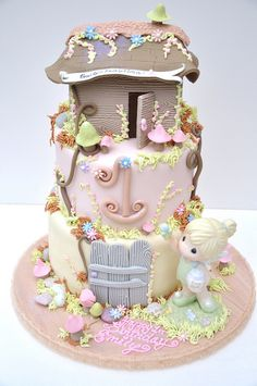 Beautiful three tier little girls fairy house birthday cake.  Pastel colors, with flowers, gates, mushrooms and a fairy house trimmed with flowers