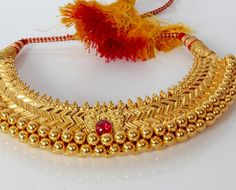 'Thushi' - Maharashtrian, Indian traditional gold necklace. You can buy it in real gold or 1 gram gold polished (which is cheaper). Real Gold - http://pngadgiljewellers.com/ best place. The polished ones, sometimes in roadside shops or certain 'imitation jewellery' shops, best 1s I know r http://www.laxmipearls.com/ or https://plus.google.com/107446470665182813949/about?gl=de&hl=en or http://www.getit.in/pune/son-chafa/laxmi-road/near-gokhle-hall-and-ranka-jewellers/34260141.html