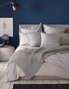 Beautiful grey bedroom inspiration with our Relaxed Denim Dove Grey. With a feature dark navy blue wall and beautiful cosy layers. Paired with woolen knit accessories and statement copper lamp. We could curl up here all day long.