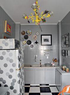 Os azulejos brancos antigos foram renovados com pintura de epóxi cinza. Os armários receberam o mesmo acabamento. Para acompanhar o espírito, a geladeira e o forno de micro-ondas ganharam adesivos em forma de bolas. Projeto do arquiteto Cesar Aumart