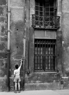 Boy drawing on a wall in the street - Paris - 1960 - (Photo by Nico Jesse)