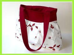 Tasche im floralen Design. Die Hintergrund-Farbe ist Weiß auf welcher wunderschöne Blätter- und Blütenranken in Rot erblühen. Das Innenfutter ist aus