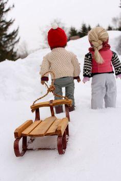 American Girl dolls sledding in winter