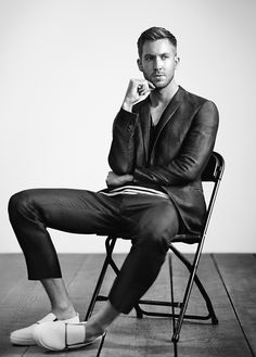 Calvin Harris for Emporio Armani S/S 2015. Slick pants and jacket with white shoes. Male model sitting in a chair.