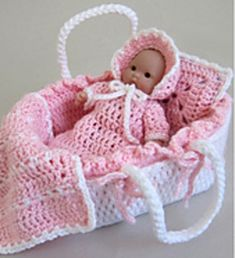 Dress up your teeny, cherished cherub in a matching two-tone bunting and bonnet, made from the softest superfine (also known as sock- or fingering-weight) yarn. Then tuck your tiny treasure into a Moses Basket to carry around with you. Inside the sturdy basket, lined with a bumper, are a lightly stuffed mattress and miniature afghan and pillow, where your precious, petite angel can rest its head.