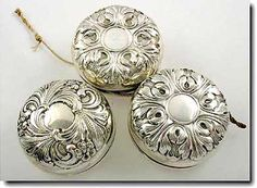 """For the little kid (or big kid) that has everything! Three repoussé sterling silver bodied yo-yos, each 2-1/4"""" in diameter, in the Art Nouveau style."""
