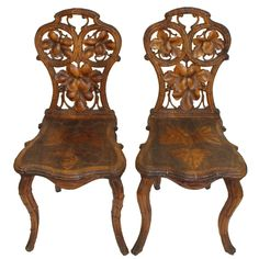 Pair of carved German black forest chestnut hallway chairs with grape vine leaf details carved in the tradition of coo coo clocks. Germany, late 19th Century. -  DANDY, Lewisburg, PA