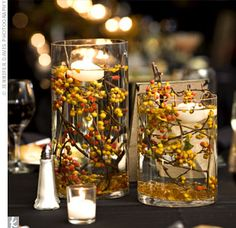 Cylinders filled with water and hibiscus berries as centerpieces