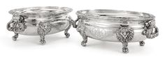 "A pair of George II silver tureens, John Wakelin & Robert Garrard, London, 1800-01 with lion mask and paw feet, dolphin-chased bail handles, engraved with palms enclosing arms under earl's coronet and motto ""NEC CUPIAS NEC METUAS"" marked on bases, each tureen with one handle marked with lion passant only length 14 1/2 in."