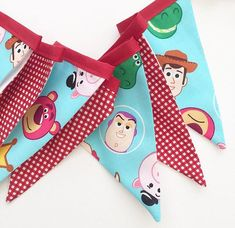 Bright and Cheerful Toy Story Themed Bunting in shades of Red and Blue  All of the flags are backed with a White Plain 100% Cotton fabric  There are a total of seven flags, measuring slightly under one metre, with excess tape at either end of the bunting for tying or pinning the bunting