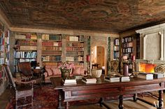 A 16th-century Italian painted ceiling crowns the pine-paneled living room/library of a house in Saint Moritz, Switzerland, with architecture and interior design by Studio Peregalli