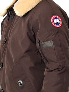 Dark-brown bomber jacket with a button and concealed zip front fastening, buttoned flap side pockets and a wide collar with a detachable cream shearling collar. Padded with duck down, this Foxe coat from Canada Goose is the perfect choice for winter. Its aviator-style collar makes it ideal for the city and the slopes.