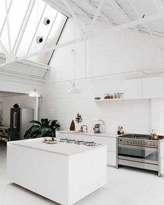 Generous white industrial kitchen photography studio in East London. Though I know that only the minority of us live in a former factory (this one is a former print factory) we can certainly dream about a kitchen like this and learn from what really makes this place so special. Besides of the ceiling height and the overall industrial look it's all about light and simplicity. The ceiling skylights and windows in combination with this all-white kitchen with an exposed brick wall and concrete…