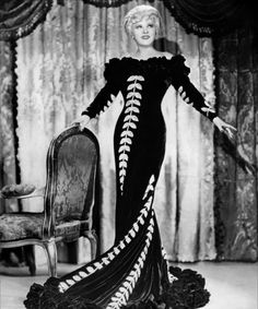 "Mae West showcasing a stunning blue velvet gown created by Travis Banton for ""Belle of the Nineties""."