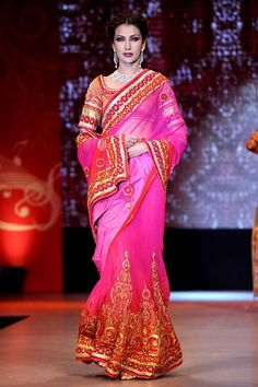 Satya Paul A lehenga sari that is rendered beautifully by shades of red and fuchsia, embellished further by velvet, frames and a touch of by Eva
