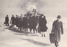 Passengers carrying their luggage were forced to walk from ferry boats trapped in the ice at the Straits of Mackinac in the 1930s.