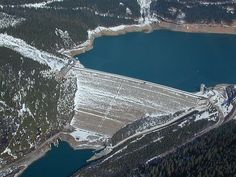 Mica Dam  (pictured left)  The Mica Dam (243 m height) is a hydroelectric dam spanning the Columbia River 135 kilometres north of Revelstoke, British Columbia, Canada.  Photo By DAR56 at en.wikipedia [Public domain], from Wikimedia Commons