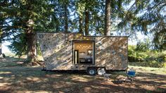 A climbing wall covers one side of this small mobile home by American company Tiny Heirloom, which features adjustable furniture