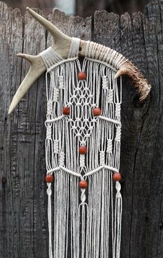 Macramé wall hanging on deer antlers with vintage wood beads