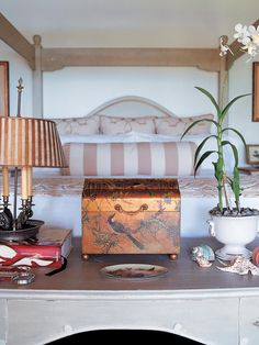 A small table at the foot of this bed contains a decorative painted chest and antique bronze lamp with a striped lampshade. A delicate white orchid adds a tranquil touch to the colorful table accessories.