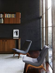 Love the dark painted brick wall, the rich timber floor, rugs and the furniture